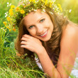 Beautiful woman in wreath of flowers lies in the green grass out — Stock Photo #30680245