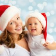 Happy family mother and baby in Christmas hats — Stock fotografie