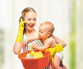 Young happy mother is a housewife with a baby does homework and — Foto de Stock