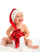Happy baby in a Christmas hat with a gift isolated — Stockfoto
