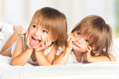 Happy little girls twins sister in bed under the blanket having — Stock Photo