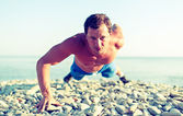 Male athlete trains pushed on the nature on the beach — Stock Photo