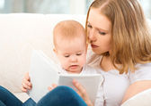 Mother reading a book a little baby on the sofa — Stock Photo