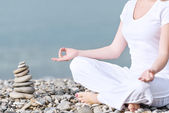 Hand of woman meditating in a yoga pose on beach — Stock Photo