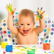 Happy child draws with colored paints hands — Stock Photo #31641347