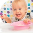 Happy baby child eats itself with a spoon — Stock Photo #31641389