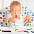 Stock Photo: Happy baby child draws with colored pencils crayons