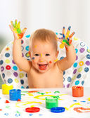 Happy child draws with colored paints hands — Photo