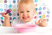 Happy baby child eats itself with a spoon — Stock Photo