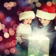 Christmas magic gift box and a happy family mother and baby — Stock Photo