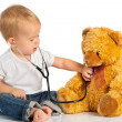 Baby plays in doctor toy bear and stethoscope — Stok fotoğraf