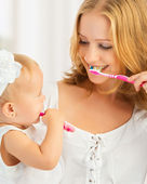 Mother and daughter baby girl brushing their teeth together — Stock Photo