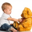 Baby plays in doctor toy bear and stethoscope — 图库照片