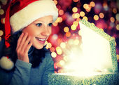 Happy woman in a Christmas cap opens the magic box — Stock Photo