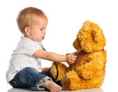 Baby plays in doctor toy bear and stethoscope — Stock Photo