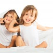 Happy little girls twins sister in bed under the blanket having — Stock Photo #34447171