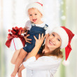 Happy family mother and baby with gift in Christmas hats — Stock Photo