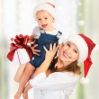 Stock Photo: Happy family mother and baby with gift in Christmas hats