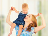 Happy family. baby sits astride the shoulders of the mother — Stock Photo