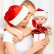Happy family mother and children with gift in Christmas hats — Stock Photo #35038959