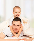 Happy family. Dad and son playing in bed — Stock Photo