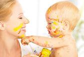 Bebé feliz sucio drena las pinturas en el rostro de la madre — Foto de Stock