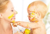 Happy dirty baby draws paints on her face of mother — Stock Photo