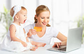 Mother and baby with a laptop and credit card — Stock Photo