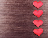 Four red hearts on a dark wooden board — Stock Photo