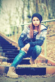 Lonely girl teenager in hat sitting on stairs and sad autumn — Stock Photo