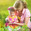 Happy family. Mom and baby in a meadow in the summer in the park — Stock Photo #39006375