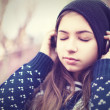 Teenage girl in headphones listens to music with closed eyes — Stock Photo