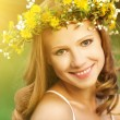 Beautiful woman in wreath of flowers lies in the green grass out — Stock Photo #39006495