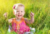 Happy baby girl on meadow on the nature — Zdjęcie stockowe
