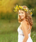Beautiful woman in wreath of flowers lies in the green grass out — Stock Photo