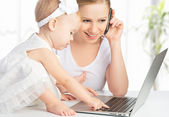 Mother with baby daughter works with a computer and phone — Stock Photo