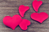 Many red hearts on a wooden board — Stock Photo
