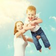Happy family. Mother throws up baby in the sky — Stock Photo