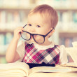 Funny baby girl in glasses reading a book in a library — Stock Photo