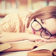 Tired student girl with glasses sleeping on books in library — Stock Photo