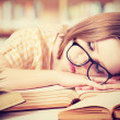 Tired student girl with glasses sleeping on books in library — Stock Photo #41477175