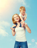 Happy family. baby sits astride the shoulders of the mother and  — Stock Photo