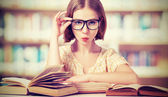Funny girl student with glasses reading books — Stock Photo