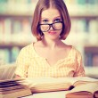 Stock Photo: Funny girl student with glasses reading books