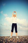 Kvinnan i vit göra yoga och sport övningar på stranden — Stockfoto