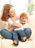 Happy family. Mother and baby daughter at home on the sofa — Stock Photo
