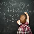 Baby girl pupil draws a chalk on blackboard — Stock Photo #43022891