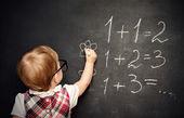 Baby girl pupil draws a chalk on blackboard — Stock Photo