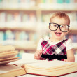 Funny baby girl in glasses reading a book in a library — Stock Photo #43490629