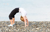 Woman doing yoga and sport exercises on  beach — Stock Photo